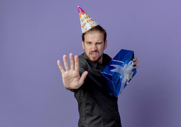 Gieriger gutaussehender mann in der geburtstagskappe steht seitlich und hält geschenkbox und gestikulierendes stopphandzeichen lokalisiert auf lila wand