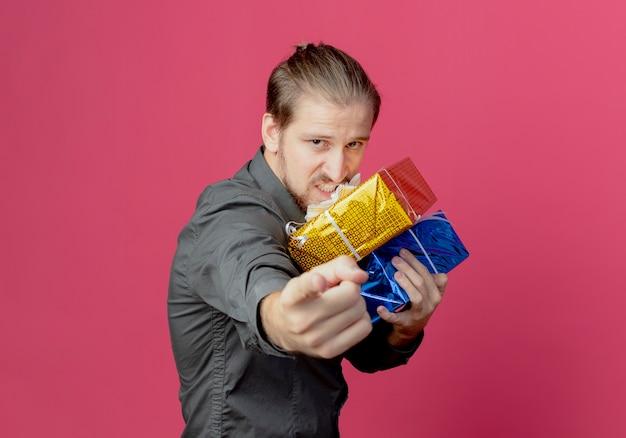 Gieriger gutaussehender mann steht seitlich und hält geschenkboxen, die isoliert auf rosa wand zeigen
