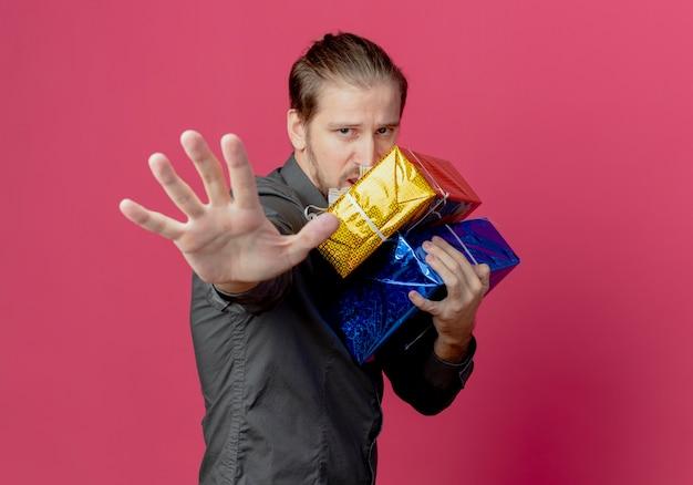 Gieriger gutaussehender mann steht seitlich und hält geschenkboxen, die stopp-handzeichen gestikulieren, lokalisiert auf rosa wand