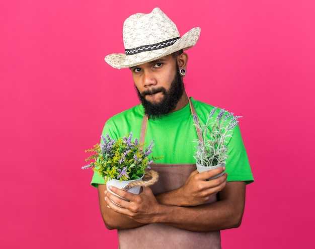 Gieriger junger gärtner afroamerikanischer typ mit gartenhut, der blumen im blumentopf hält und kreuzt