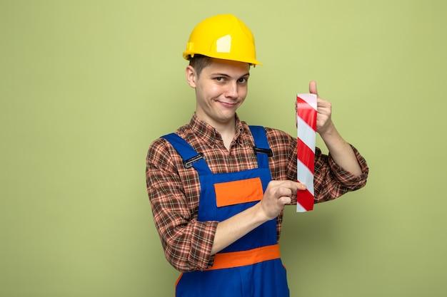 Gieriger junger männlicher baumeister in uniform mit klebeband