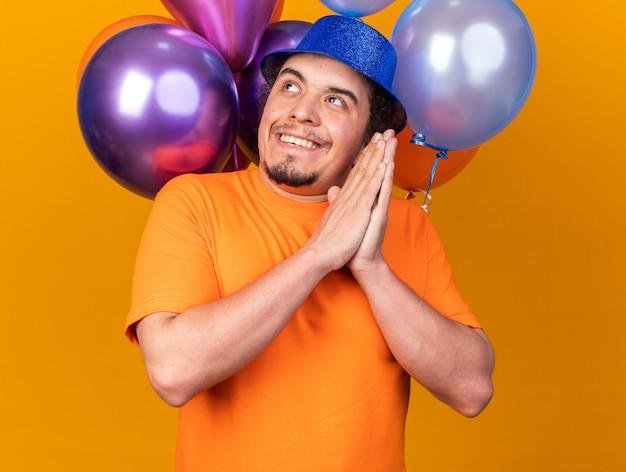Gieriger junger mann mit partyhut, der vor ballons steht und die hände zusammenhält, isoliert auf oranger wand