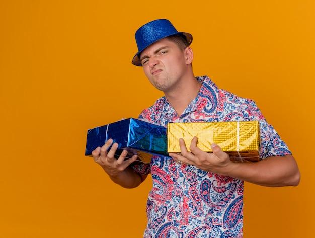 Gieriger junger party-typ, der blauen hut trägt, der geschenkboxen isoliert auf orange hält