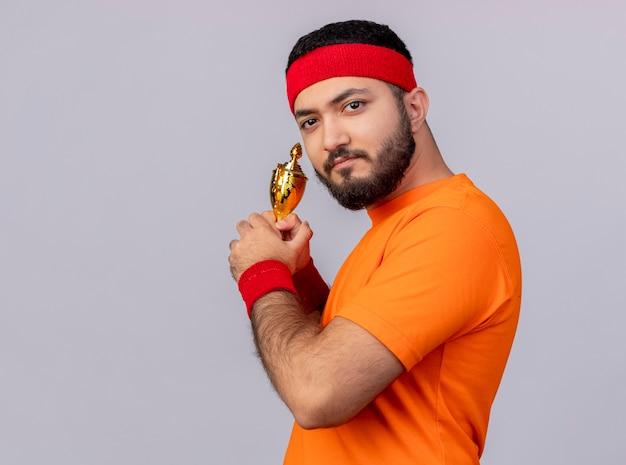 Gieriger junger sportlicher mann, der stirnband und armband hält, die gewinnerpokal lokalisiert auf weißem hintergrund mit kopienraum halten