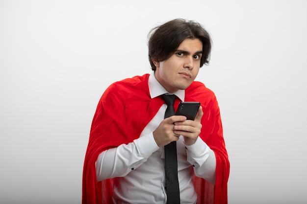 Gieriger junger superheld, der kamera betrachtet, die krawatte hält telefon lokalisiert auf weiß