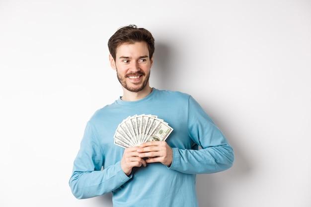 Gieriger lächelnder mann, der geld zeigt und nach rechts schaut, über das einkaufen nachdenkend, über weißem hintergrund stehend.