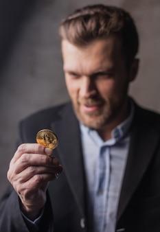 Gieriger mann, der bitcoin betrachtet. fokus auf münze