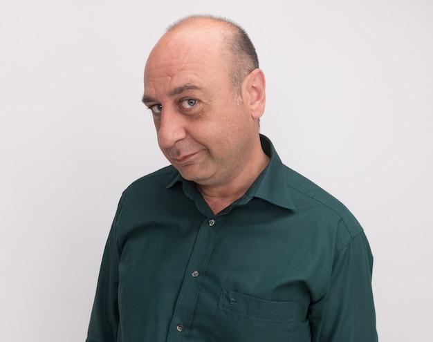 Gieriger mann mittleren alters, der grünes t-shirt trägt, das auf weißer wand lokalisiert wird