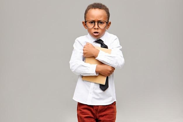 Gieriger nerdiger dunkelhäutiger grundschüler in schuluniform und brille mit festem heft und ausruf. konzept für kindheit, bildung, lernen und lebensstil