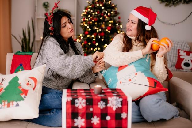 Gieriges hübsches junges mädchen mit weihnachtsmütze hält orangen und schaut ihre freundin mit stechpalmenkranz an, die auf sesselweihnachtszeit zu hause sitzt