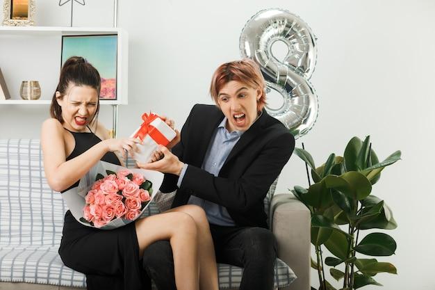 Gieriges junges paar am glücklichen frauentag, das geschenk mit blumenstrauß auf dem sofa im wohnzimmer hält
