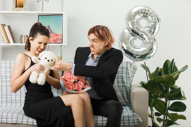 Gieriges junges paar am glücklichen frauentag, der teddybär mit blumenstrauß auf dem sofa im wohnzimmer hält