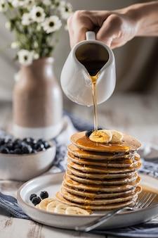 Gießen ahornsirup auf hausgemachte bananenpfannkuchen mit blaubeeren, einfache rezepte hausgemachte küche
