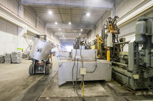 Gießen des aluminiummetalls von der pfanne zur lademaschine in einen großen behälter Premium Fotos
