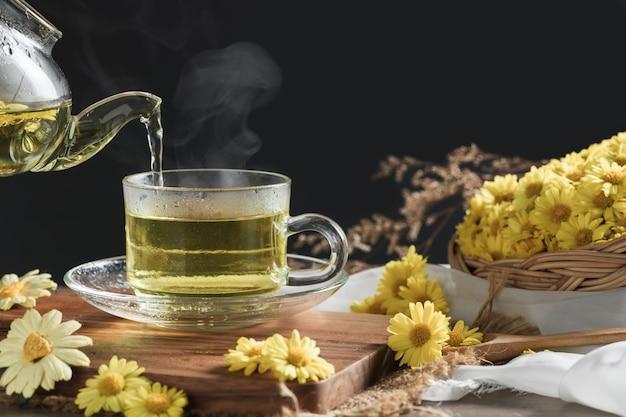 Gießen heißen chrysanthementee mit heißem dampf und chrysanthemenblume im korb auf schwarz