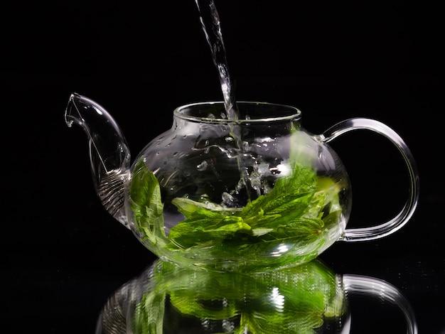 Gießen heißes wasser in eine glasteekanne auf schwarzem hintergrund grüner minztee kräutertee und gesund