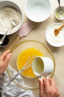 Gießen öl über eier in glasschüssel. einen kuchen in der glasschüssel kochen, draufsicht. schritt für schritt rezept.