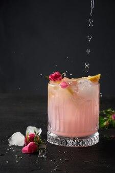 Gießen rosa alkoholischer cocktail mit rosenblüten auf schwarzem hintergrund