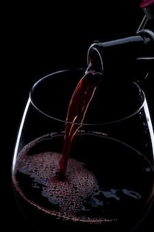 Gießen rotwein aus der flasche in das weinglas auf schwarz