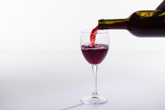 Gießen rotwein in das glas auf weißem hintergrund mit kopienraum