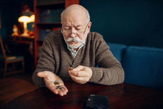 Gießen sie älteren mann hält münzen