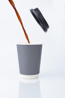 Gießen sie das kaffeewasser auf einen pappbecher mit deckel.
