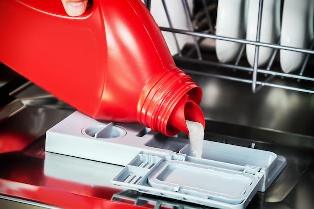 Gießen sie das pulver in die spülmaschine