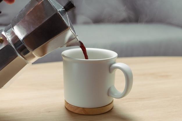 Gießen sie den kaffee in eine keramikschale