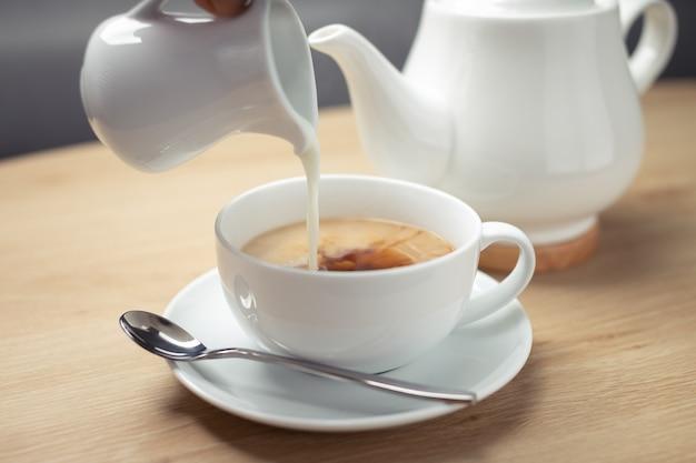 Gießen sie die milch in die kaffeemischung auf die weiße tasse.
