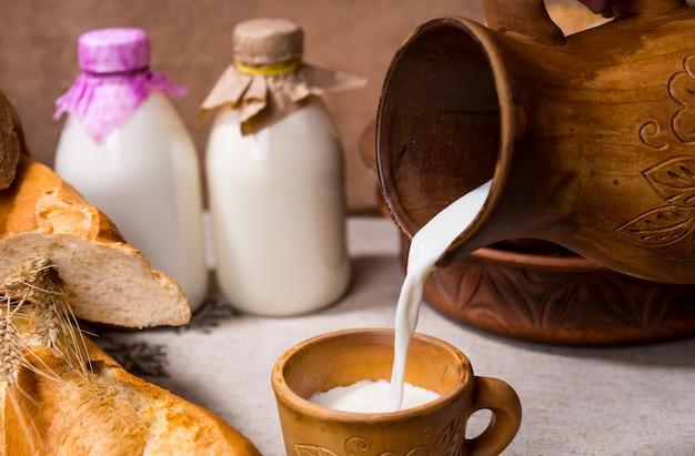 Gießen sie eine tasse frische cremige milch aus einem keramikkrug oder krug für ein leckeres frühstücksgetränk, das mit frischem brot und brötchen serviert wird
