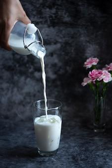 Gießen sie frische milch in ein glas mit eis.