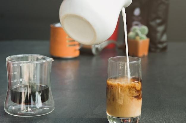 Gießen sie frische milch in eine schwarze kaffeetasse.