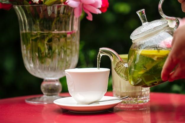 Gießen sie grünen tee aus einer glasteekanne in eine weiße tasse