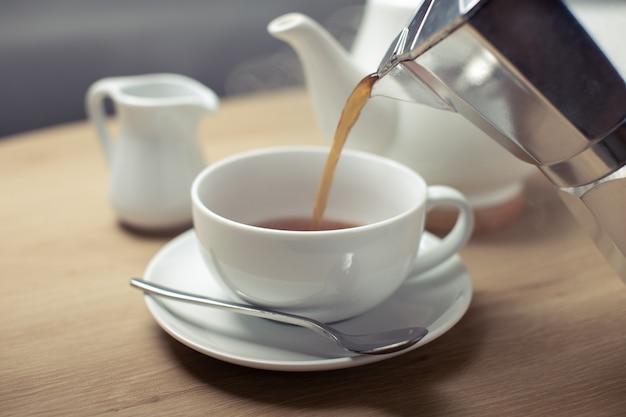 Gießen sie heißen kaffee in die weiße tasse