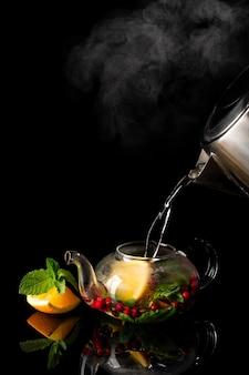Gießen sie heißen tee mit orangenminze und preiselbeeren. dampf steigt aus dem wasserkocher