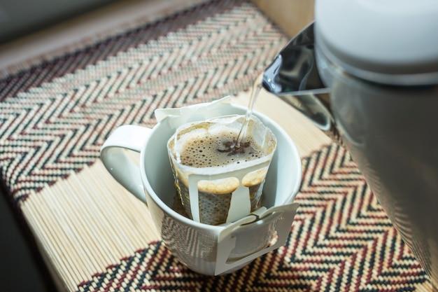 Gießen sie heißes wasser in eine tasse mit tropfkaffeebeutel, fokussieren sie selektiv.