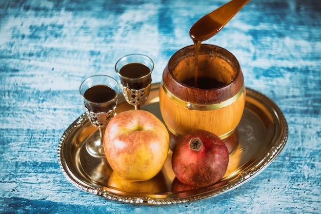Gießen sie honig auf apfel und granatapfel mit honigsymbolen des jüdischen neujahrs - rosh hashanah.