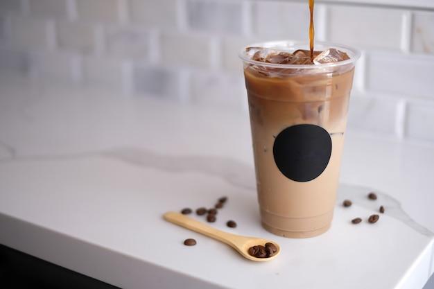 Gießen sie kalten kaffee mit der bohne auf den marmor. eis-erfrischung in der plastik-tasse zum mitnehmen.