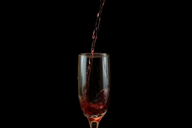 Gießen sie köstlichen rotwein in glas