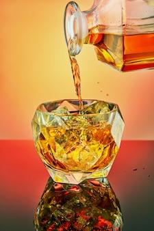 Gießen sie luxus-whisky in ein kristallglas mit eis auf einem gefälle