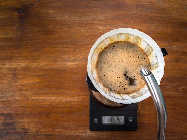 Gießen sie mit filterpapier wasser auf den leicht gerösteten kaffeesatz durch den tropfer.