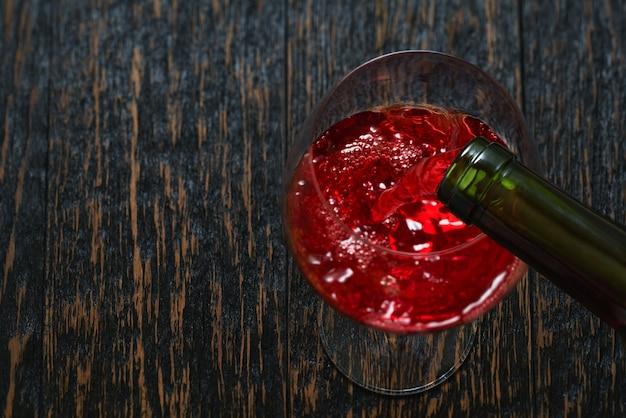 Gießen sie rotwein in ein glas auf schwarzem holztisch, draufsicht.