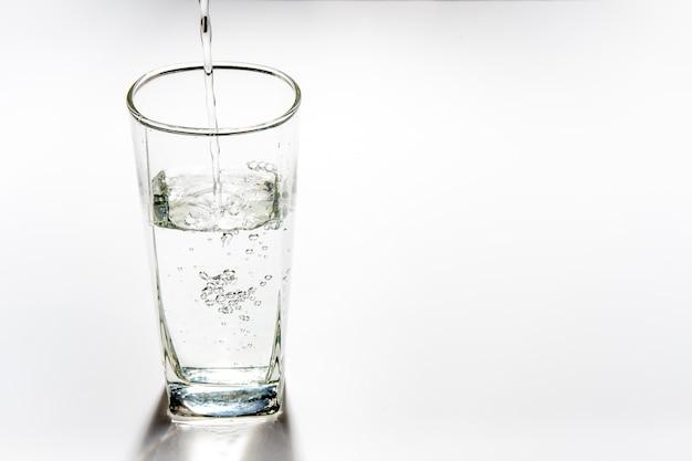 Gießen sie trinkwasser in das hohe glas