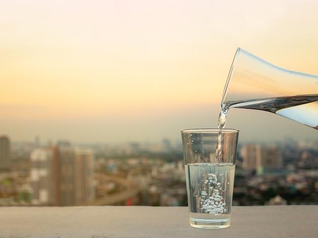 Gießen sie während des sonnenuntergangs wasser in glas auf einem betontisch auf einem verschwommenen stadthintergrund.