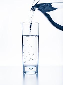 Gießen sie wasser aus einem krug in ein glas