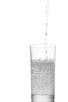 Gießen sie wasser in ein glas, das auf weiß isoliert ist