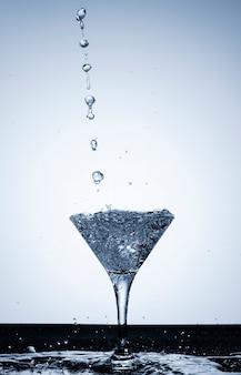 Gießen sie wasser in eine transparente glasnahaufnahme