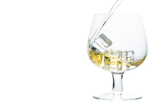 Gießen sie whisky oder brandy auf eiswürfel in snifter- oder ballonglas isoliert auf weißem hintergrund, getränkekonzept