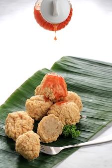 Gießen sie würzige sauce zu hausgemachtem fried chicken oder shrimps meatball (bakso goreng bandung), serviert auf bananenblättern