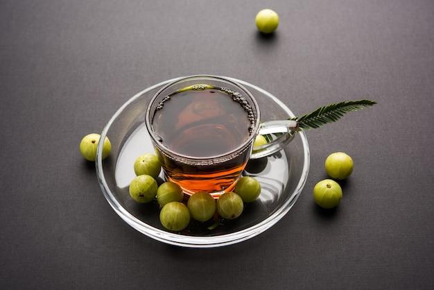 Gießen von amla-tee oder avla chai in transparente glastasse mit untertasse auf weißem oder schwarzem hintergrund. beliebte ayurveda-medizin aus indien
